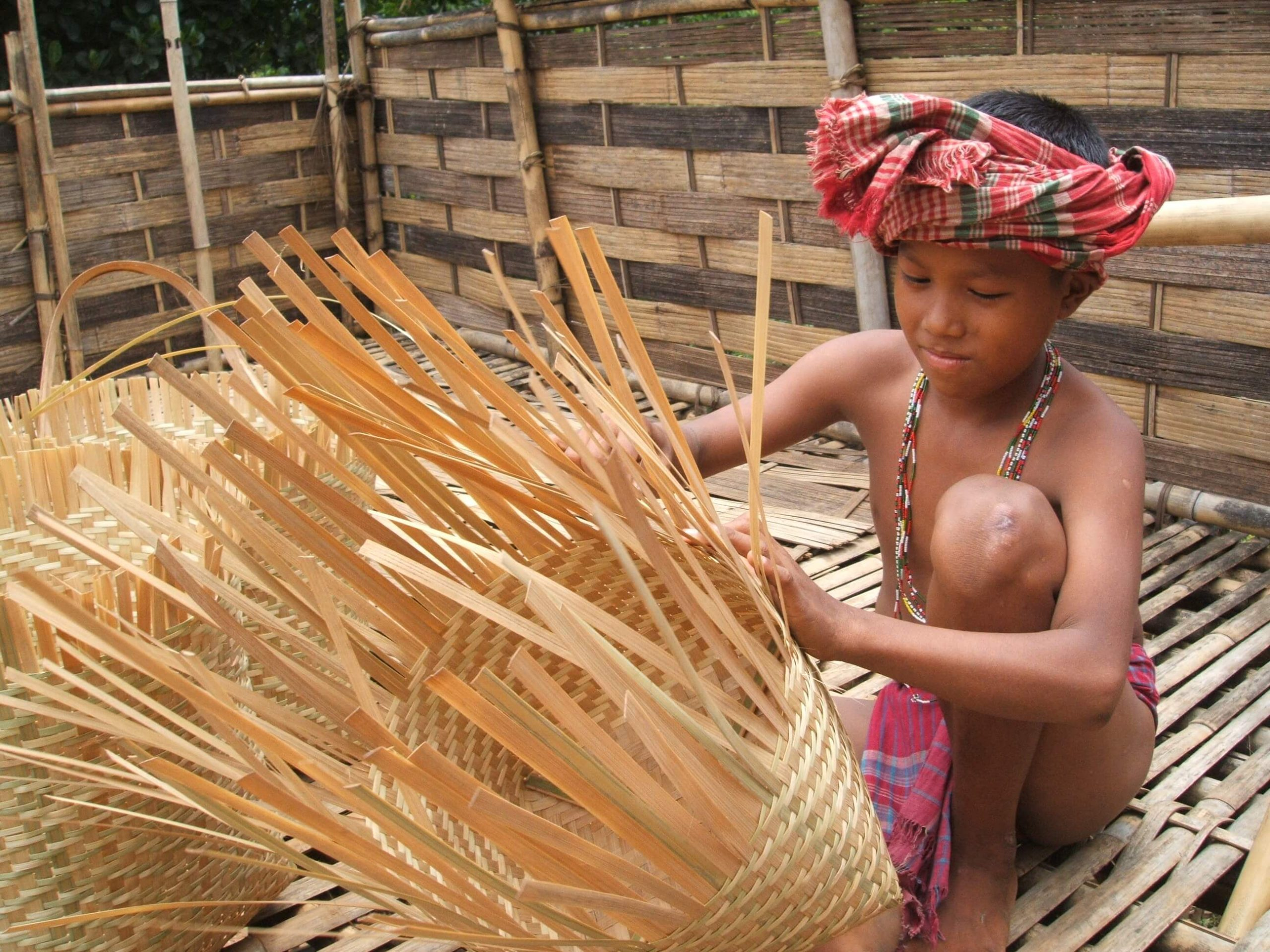 Young indigenous boy weaving bamboo craft