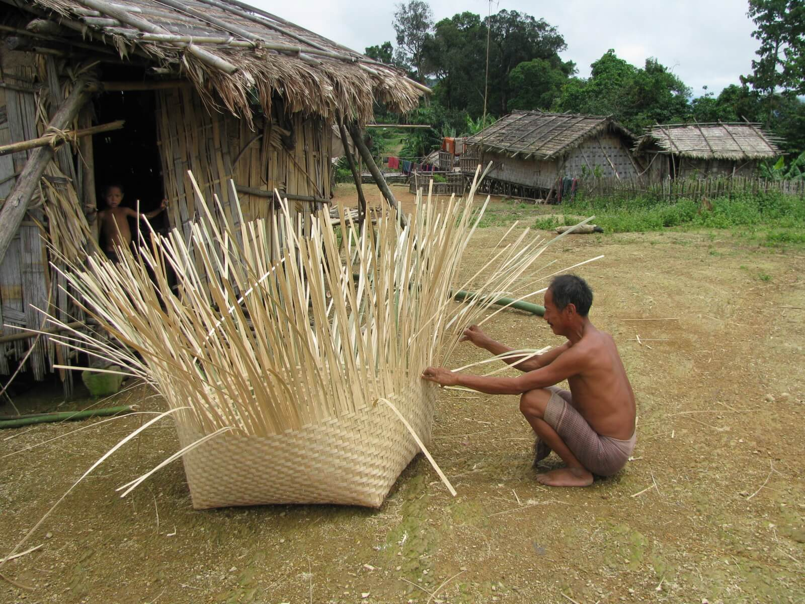Indigenous man weaving traditional equipment  with bamboo