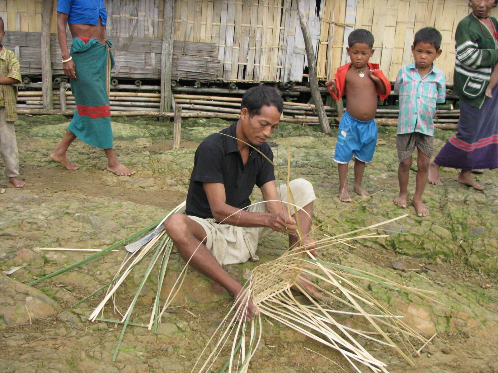 Indigenous man weaving bamboo equipment for daily use