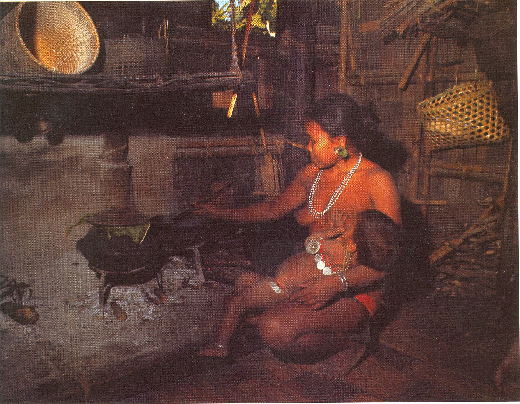 Indigenous mother feeding her child and working